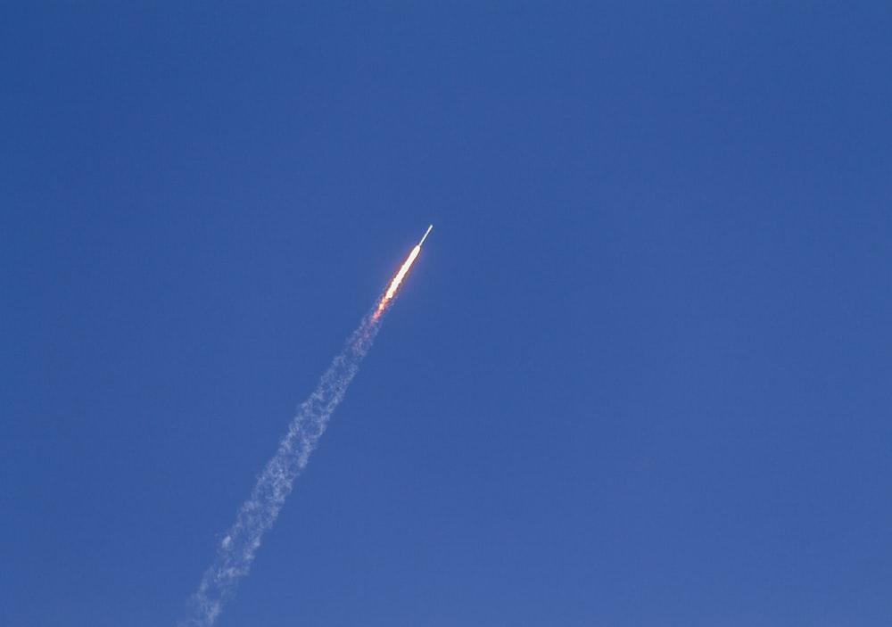 flying rocket during daytime