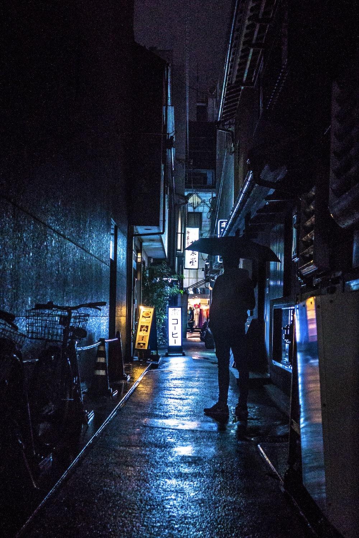 man standing under umbrella at night