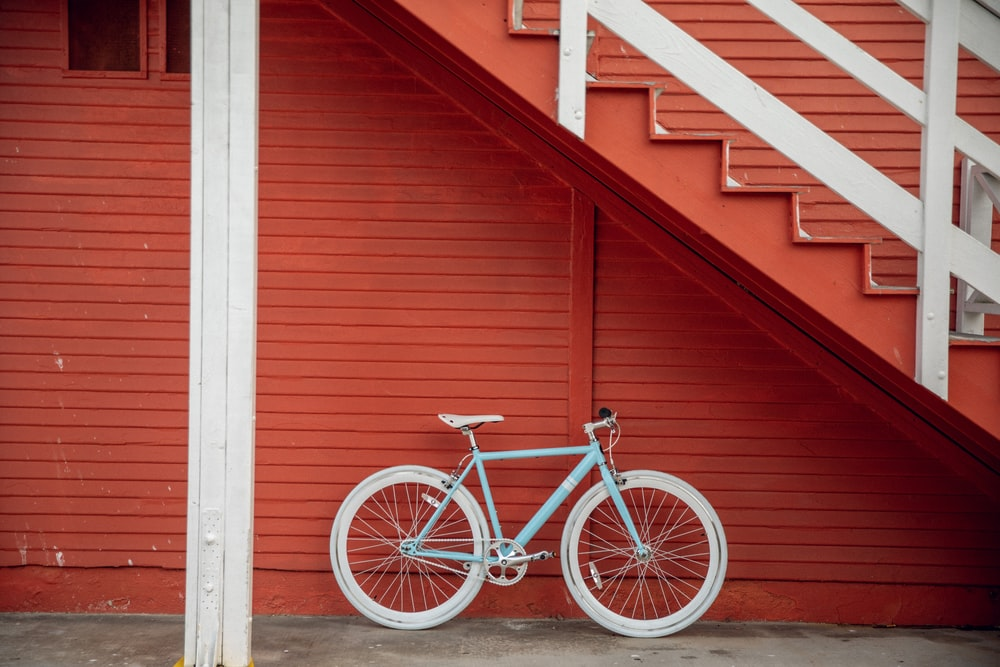 white and red bicycle with training wheels
