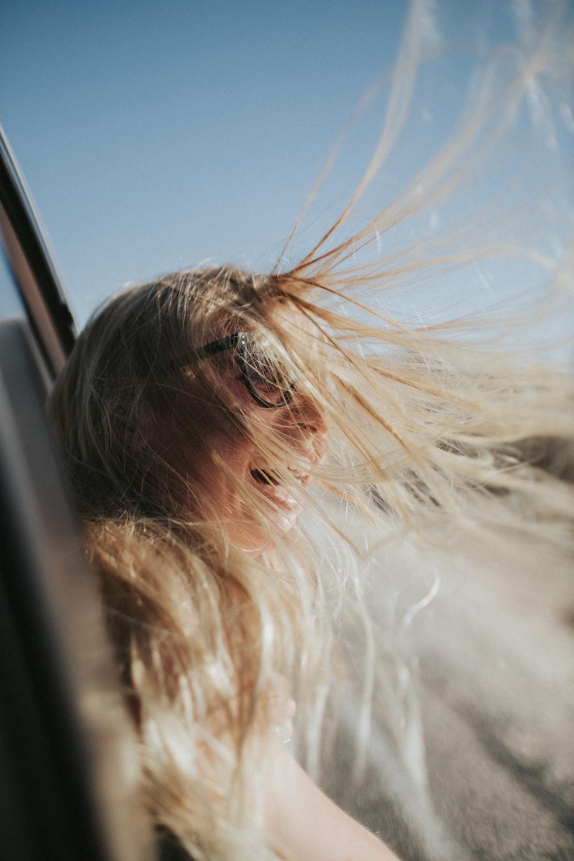 smiling woman wearing black eyeglasses riding on vehicle