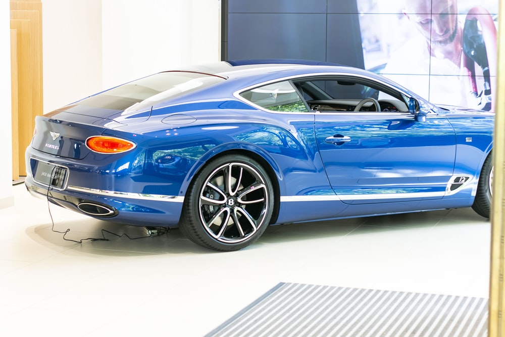 blue coupe parked beside wall