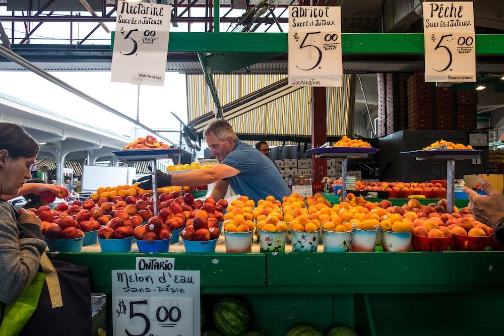 man in blue top standing beside bunch of fruits