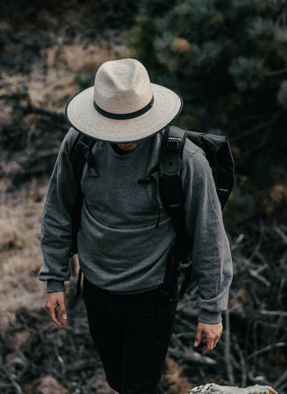 man walks and wears backpack, hat and sweatshirt
