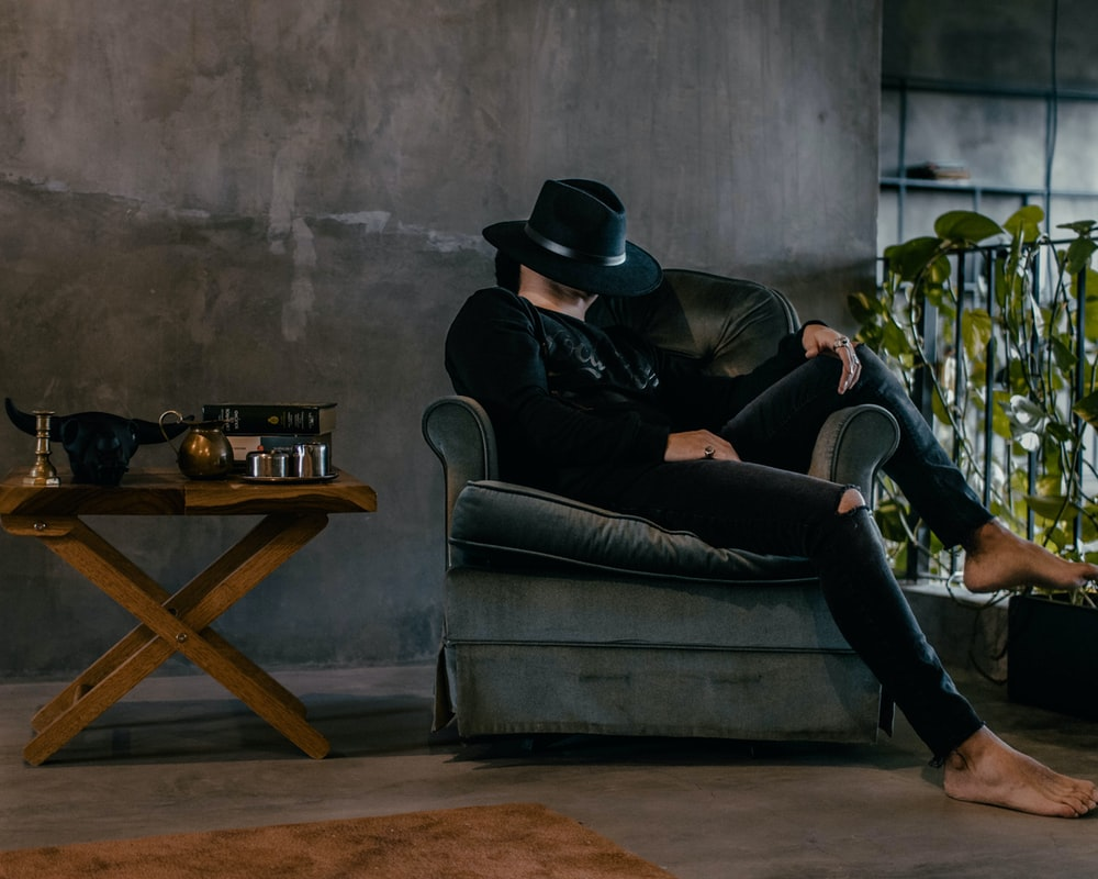man sits on sofa and covers his face with black hat