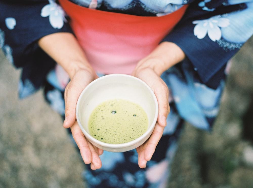 Geisha holding near empty bowl of soup