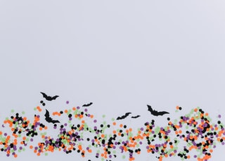 black bat and multicolored dots illustration