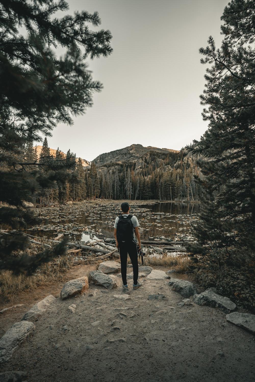 man wearing black backpack standing beside trees