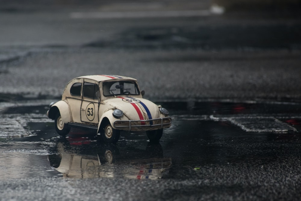 white and red Volkswagen car toy on wet road
