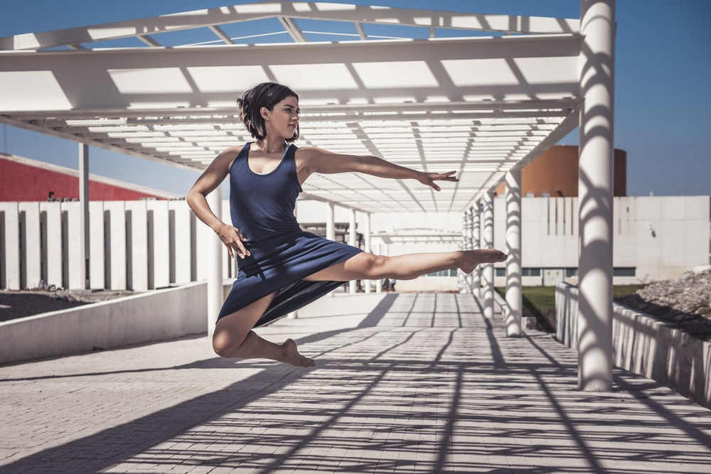 woman jumping wearing blue sleeveless dress during daytime