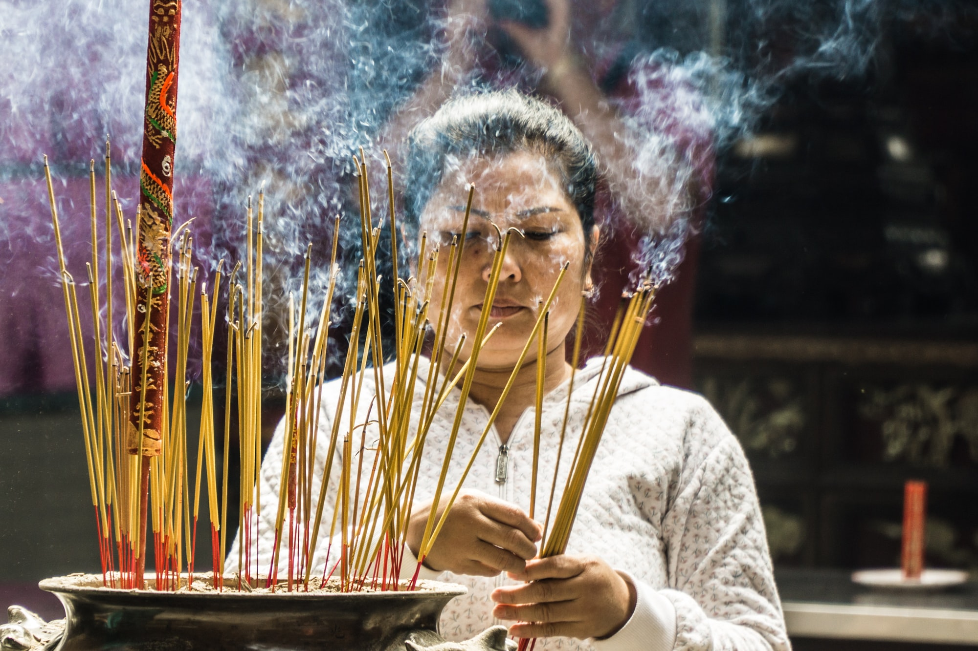 A woman takes part of a religious offering in a confucian temple in Ho Chi Minh City, Vietnam.