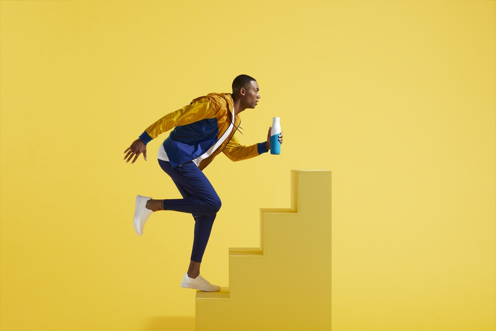 man in blue and yellow jacket and blue pants on yellow stair