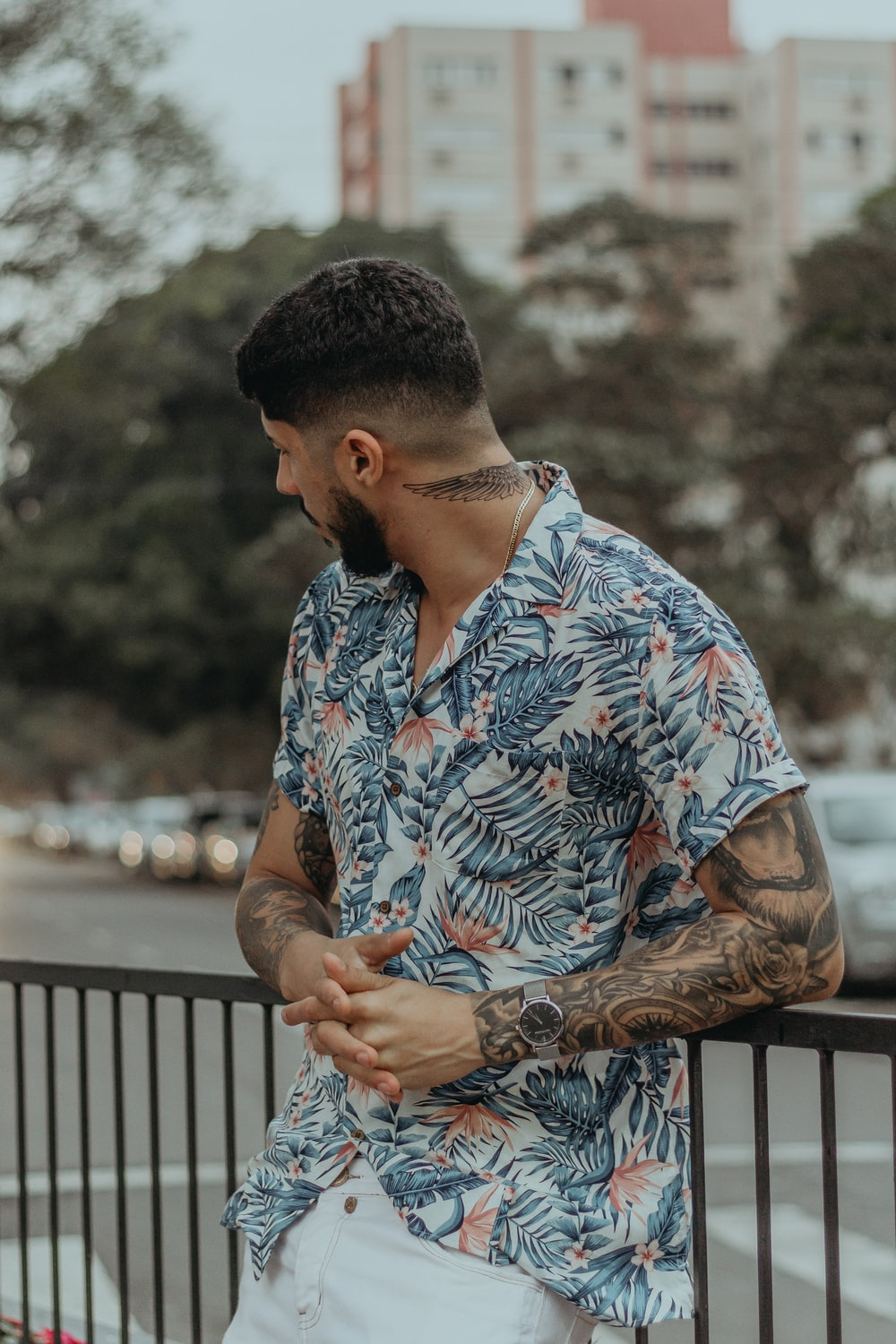 man in floral button-up shirt leaning on metal rail