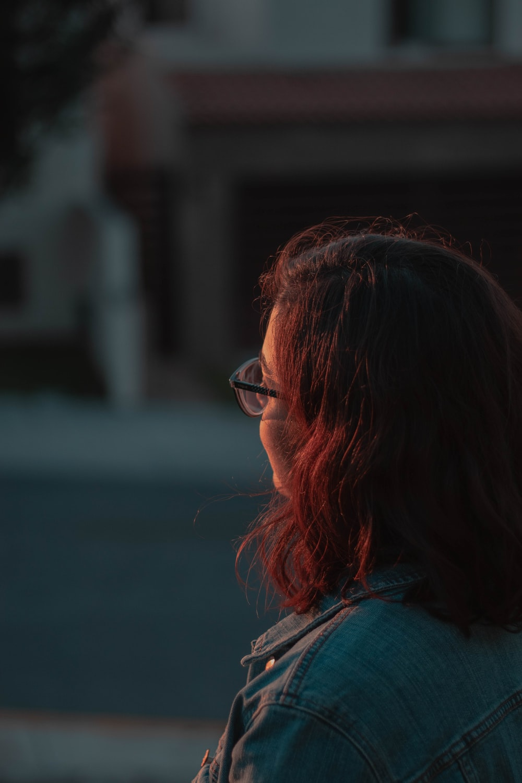 woman wearing blue denim jacket and eyeglasses during daytime