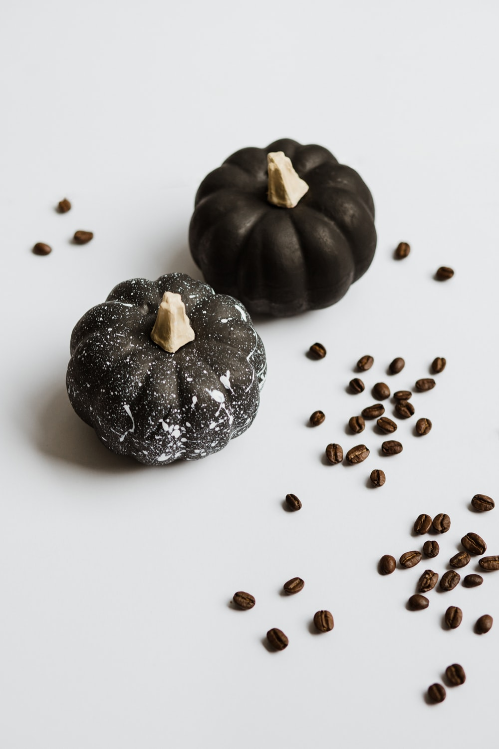 two black pumpkins on white surface