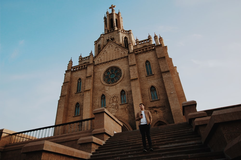 man standing on stairs in front of church during day
