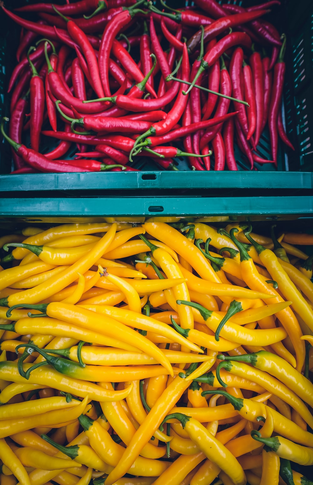 yellow and red chilis on plastic crate