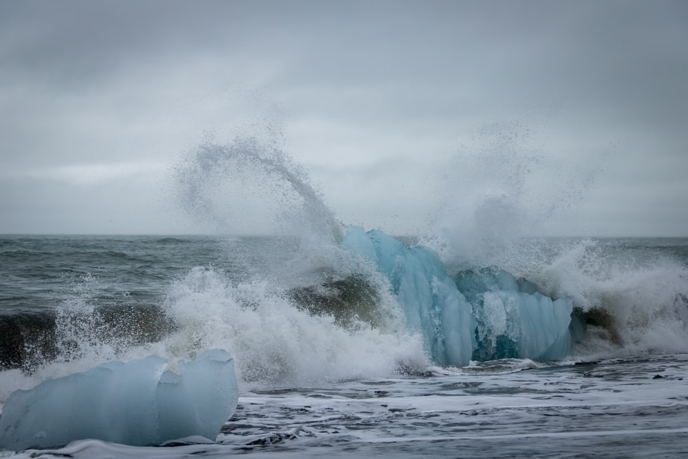 white ocean wave under white and gray sky during daytime