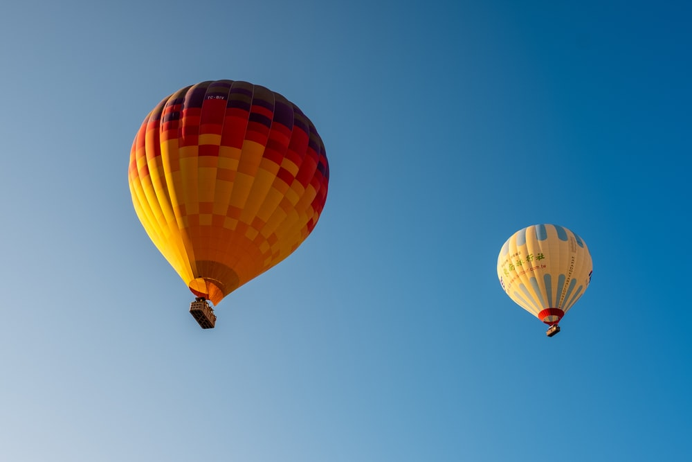 two assorted-colored hot air balloon in the sky during daytime