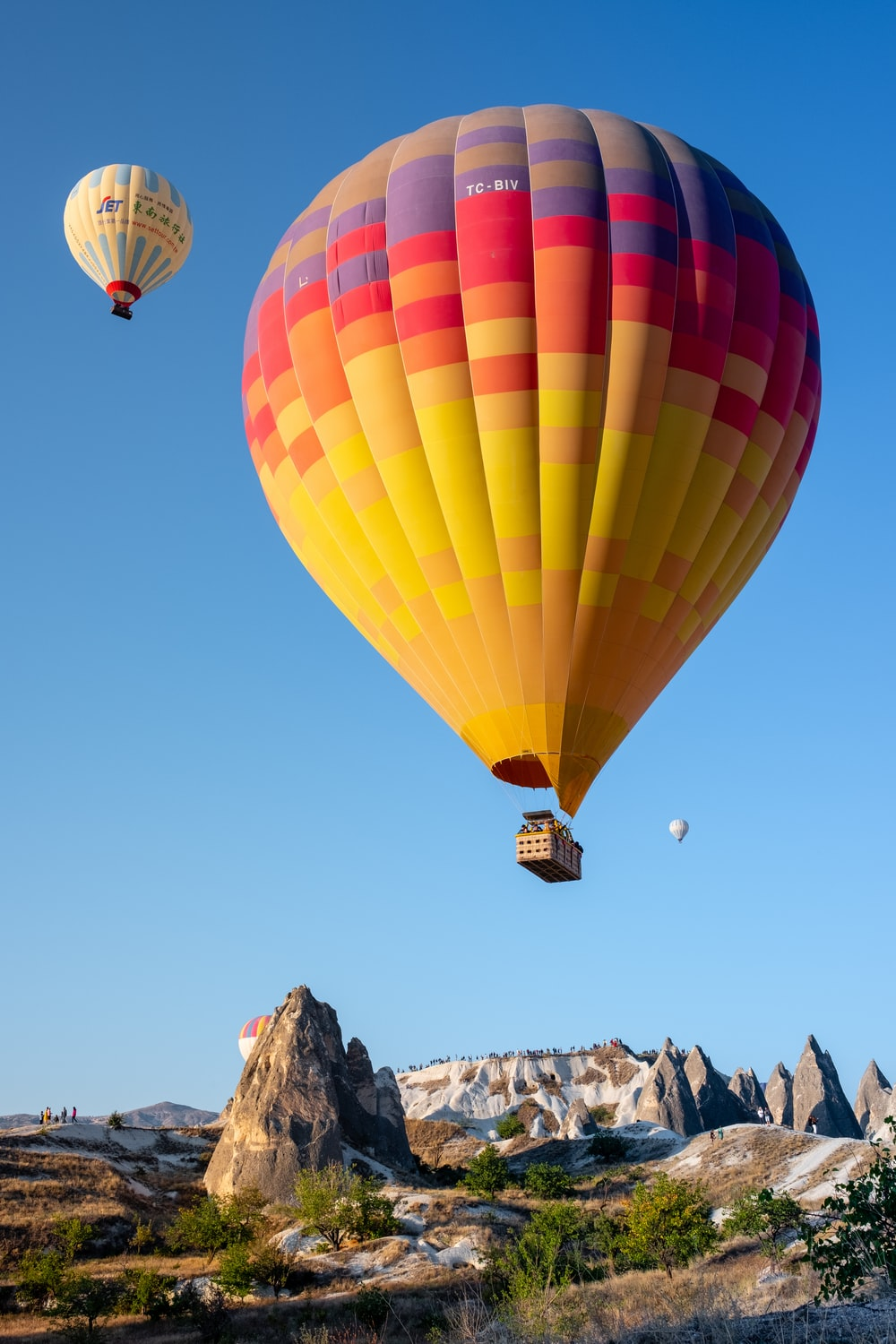 three multicolored hot air balloons above mountain during daytime