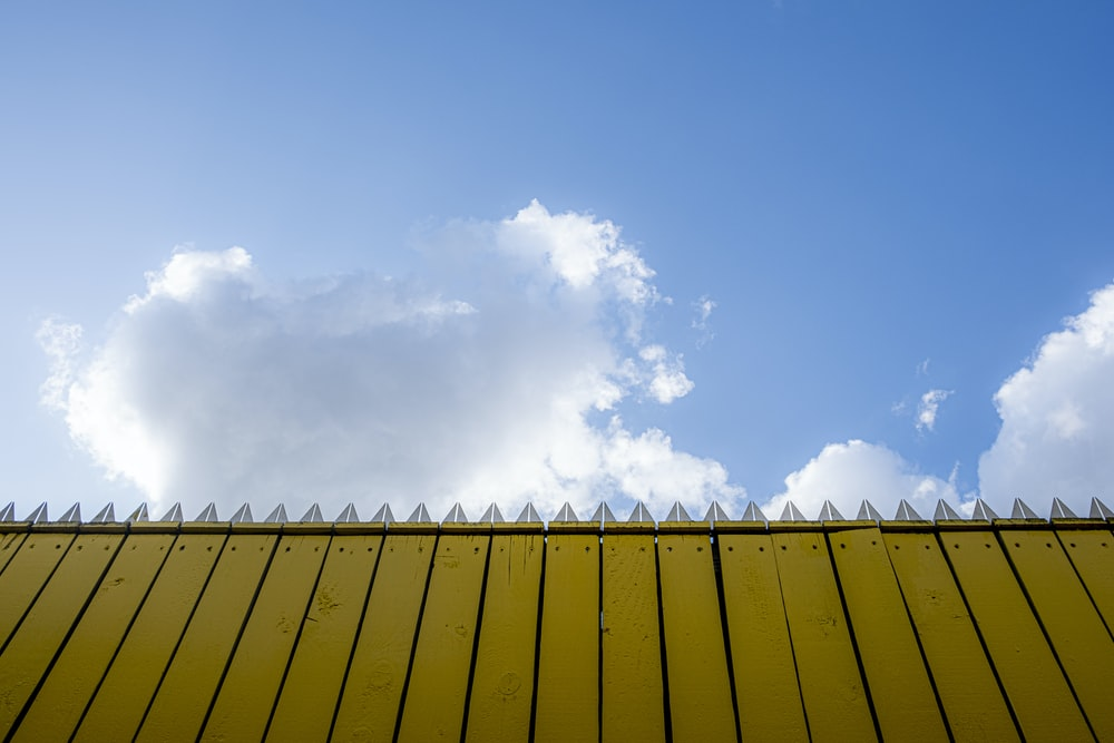 beige fence under cloudy sky
