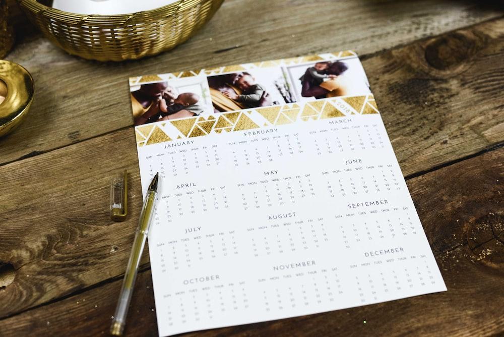 black ballpoint pen near calendar