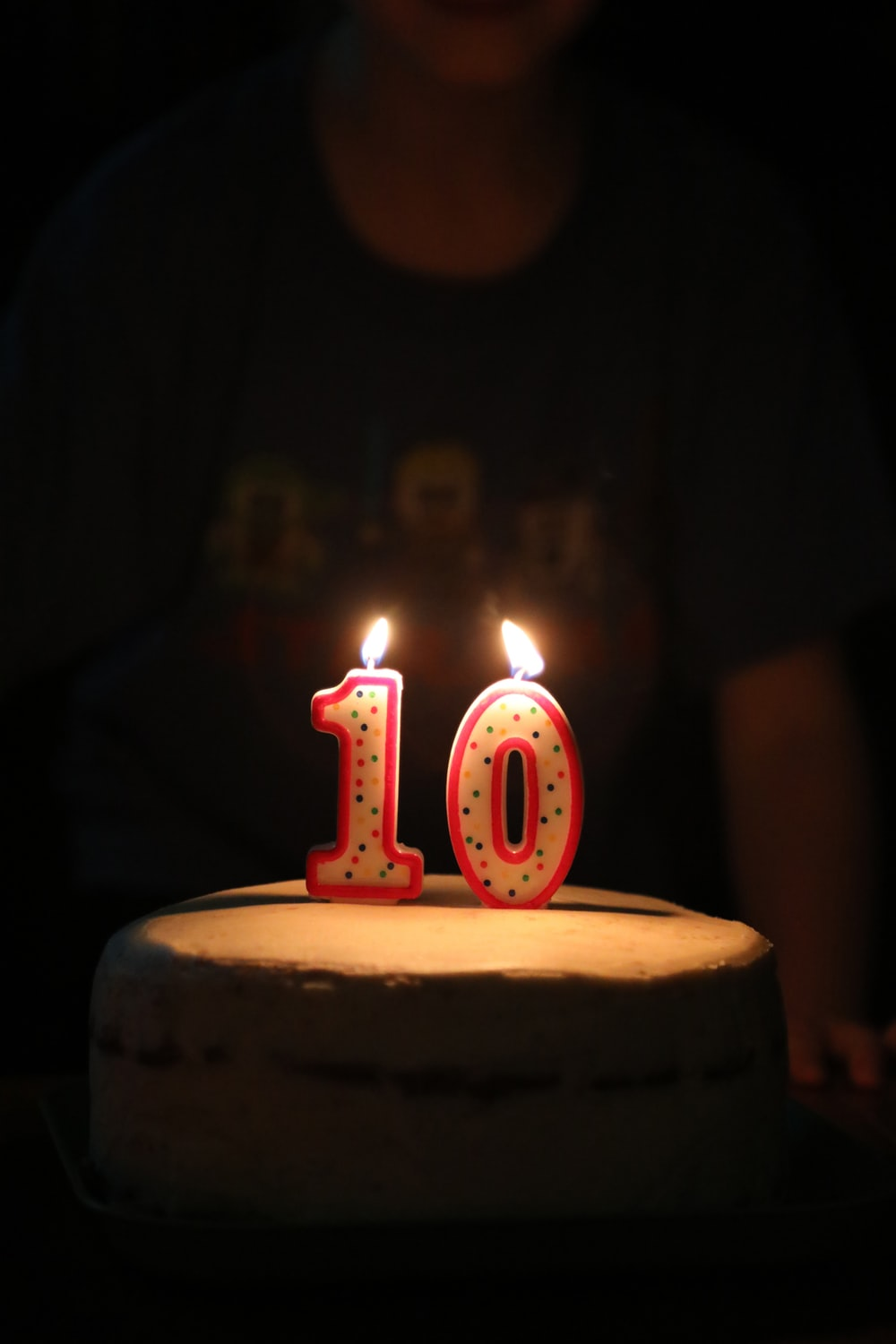 person standing beside cake with 10 candles