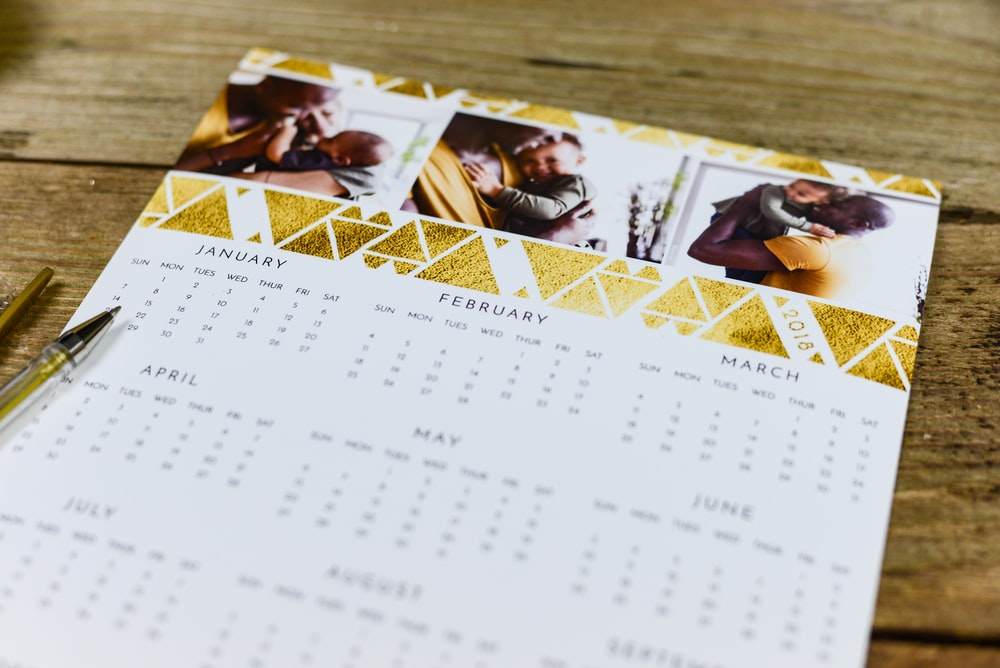 white and gold calendar on brown surface
