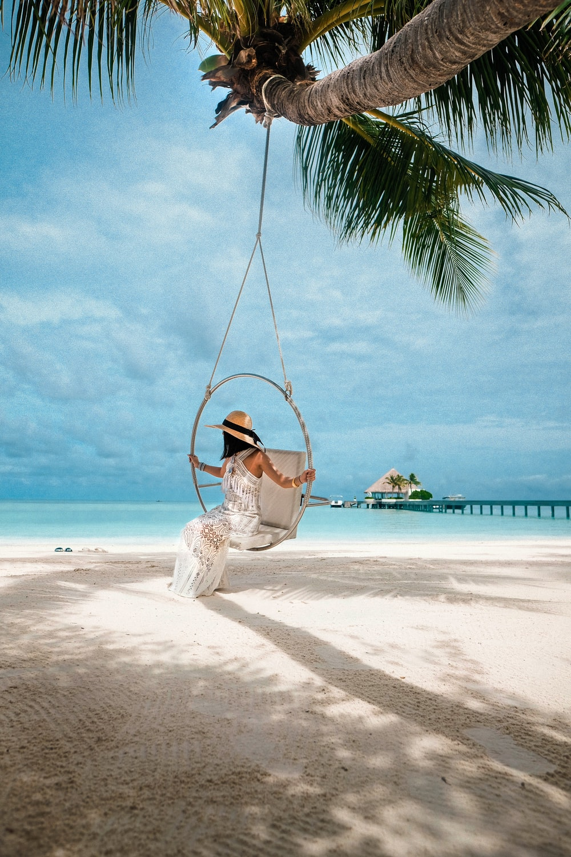 woman in white dress sitting on swing