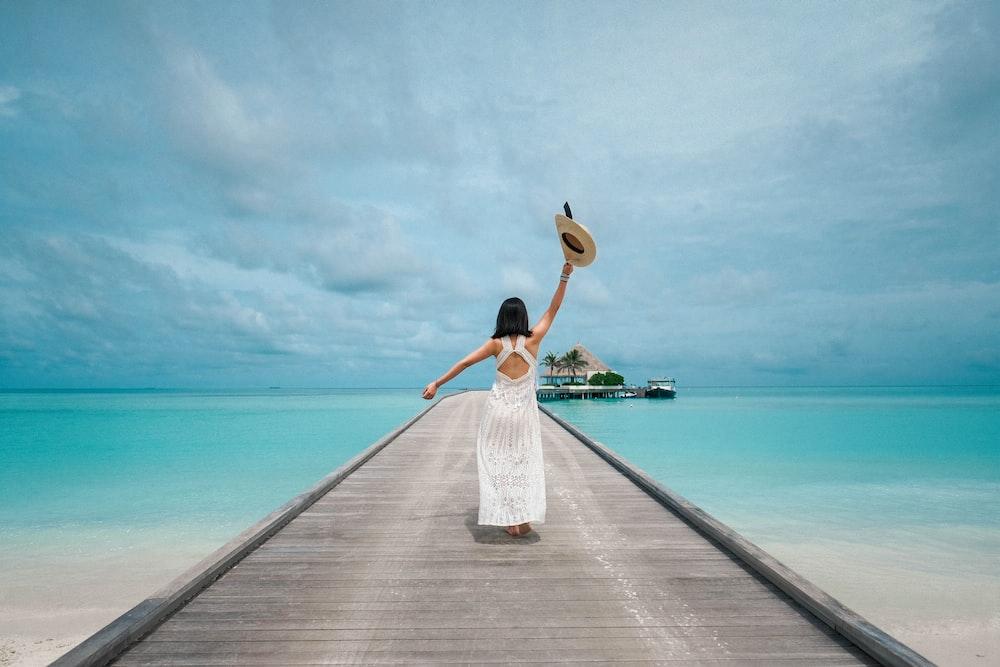 woman wearing white dress standing on sea dock