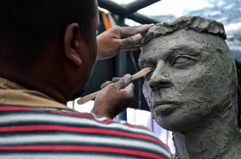 man sculpting man's eye