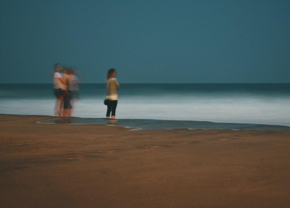 women standing on seashore