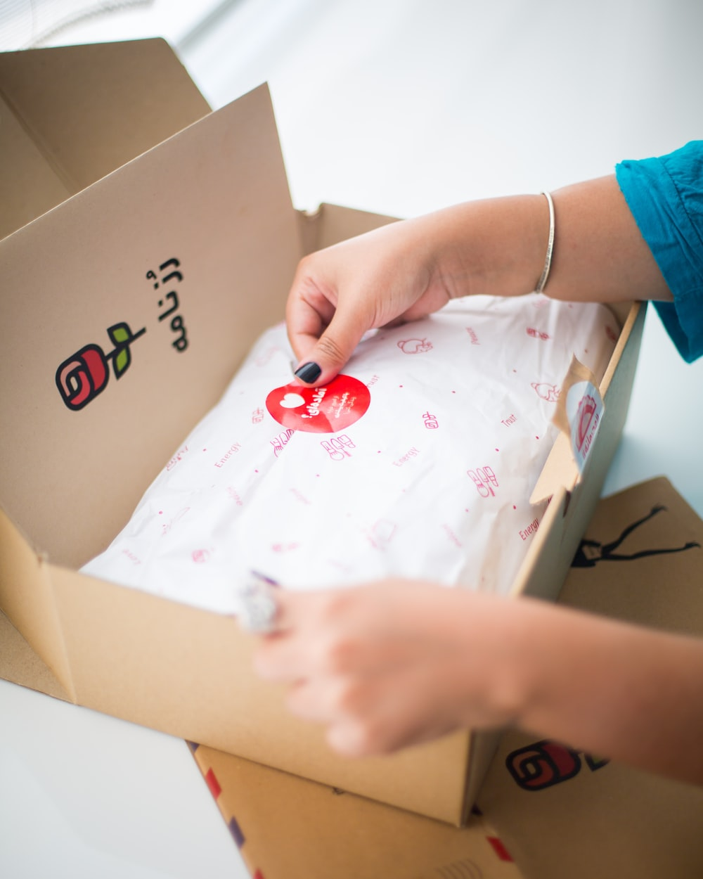 person sticking sticker on box