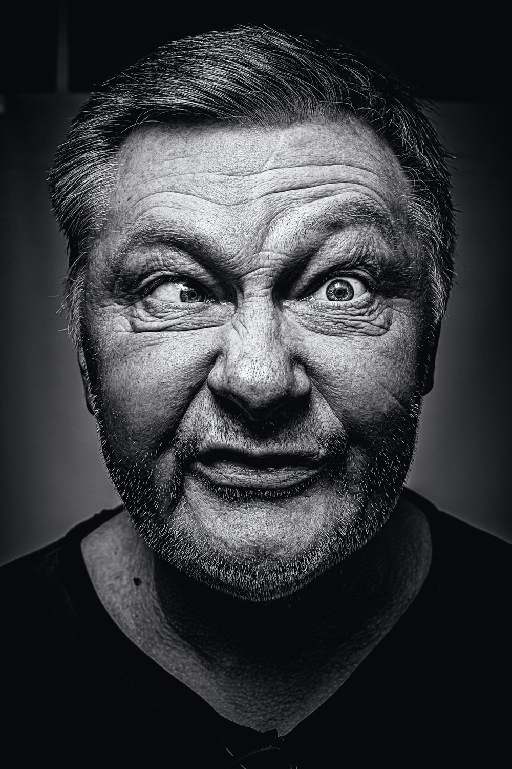grayscale photography of man making silly face