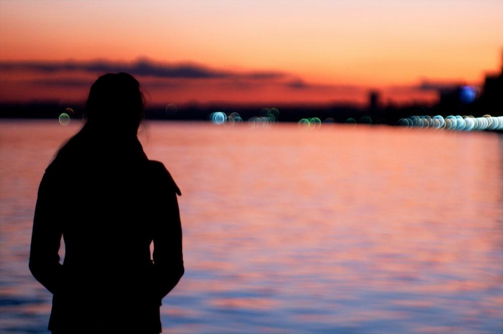 silhouette of woman near the ocean