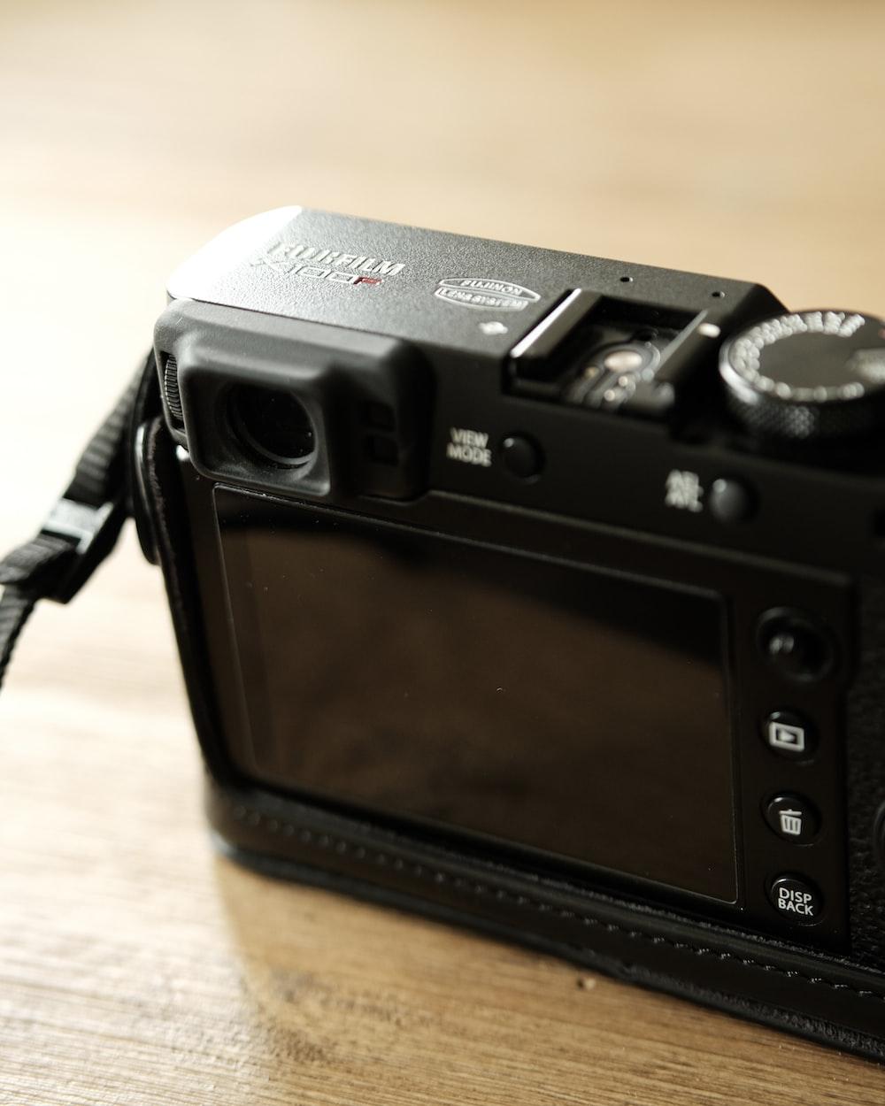 black Fujifilm camera on brown surface