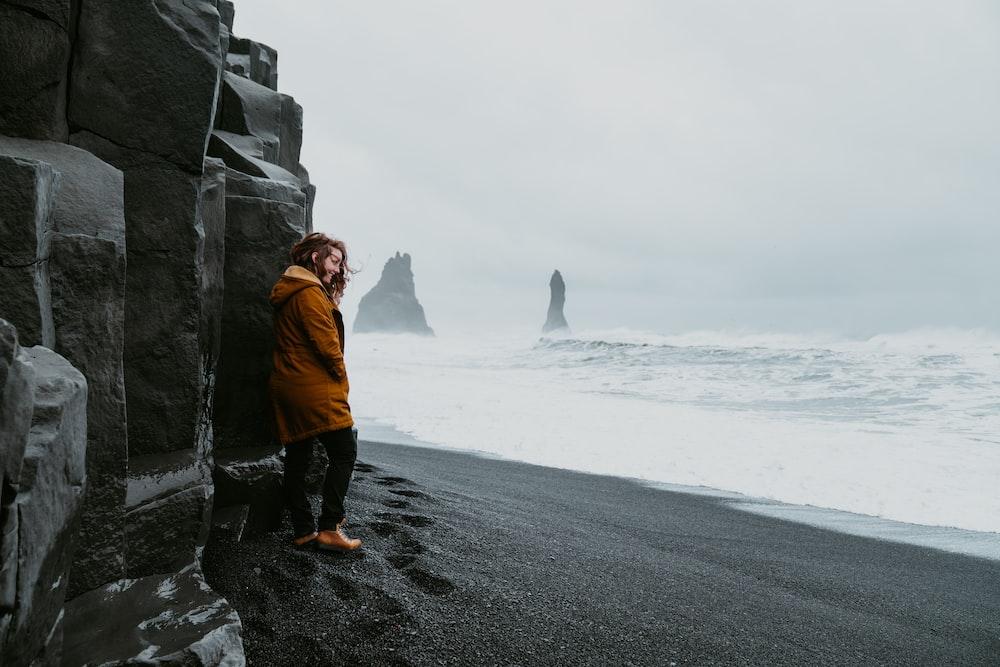 woman wears brown jacket standing near the ocean