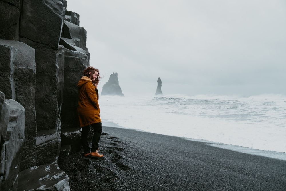 woman wears brown jacket standing near the ocean