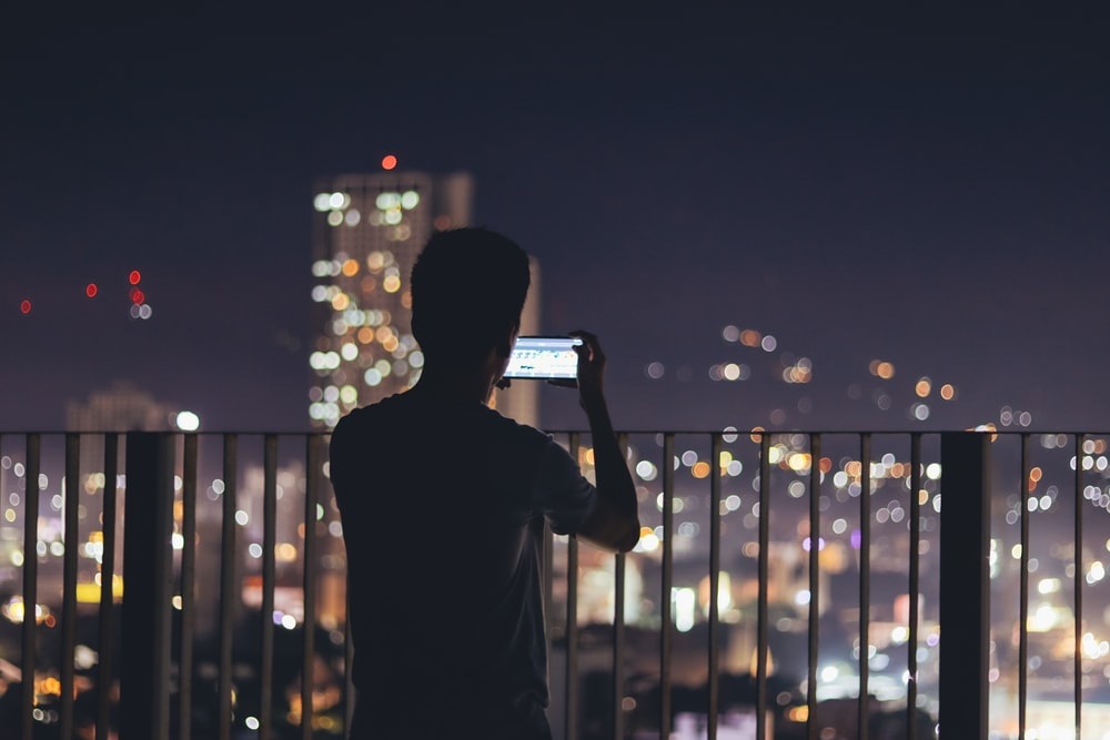 man standing in the terrace taking pictures of citylights
