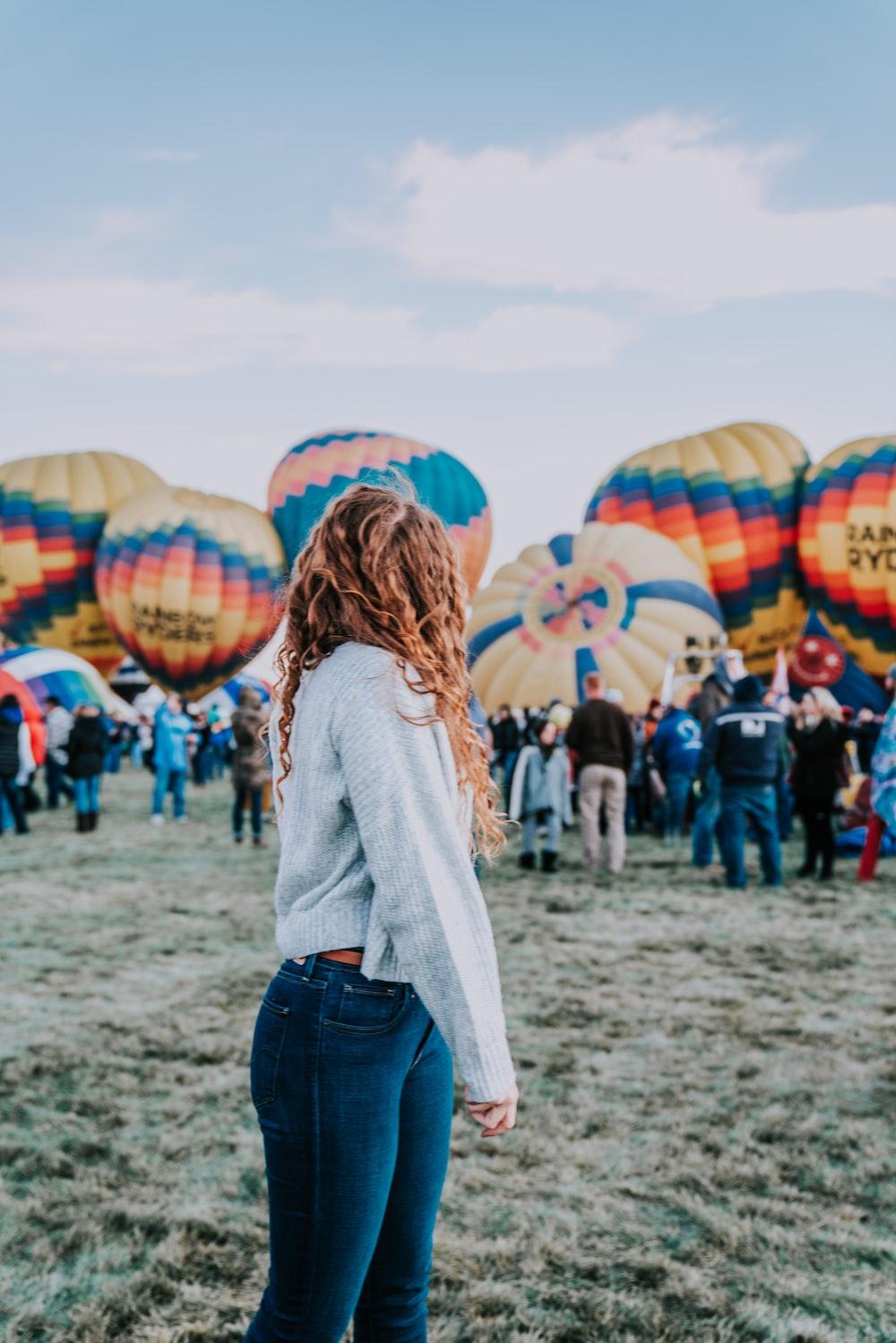 woman standing near hot air balloons