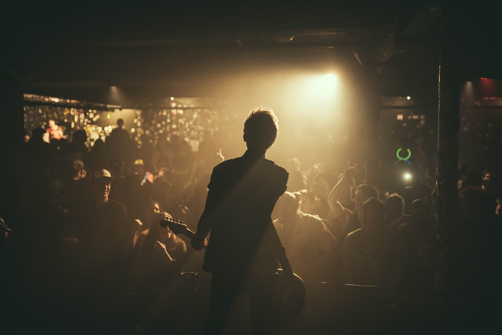 man playing guitar in front of crowd
