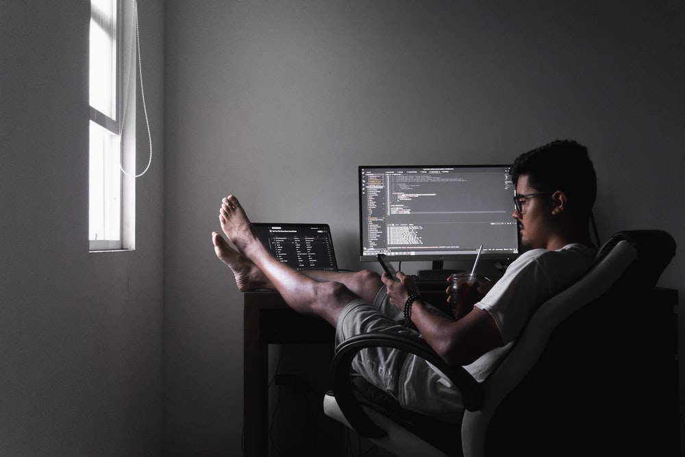 man sitting on chair infront of computer