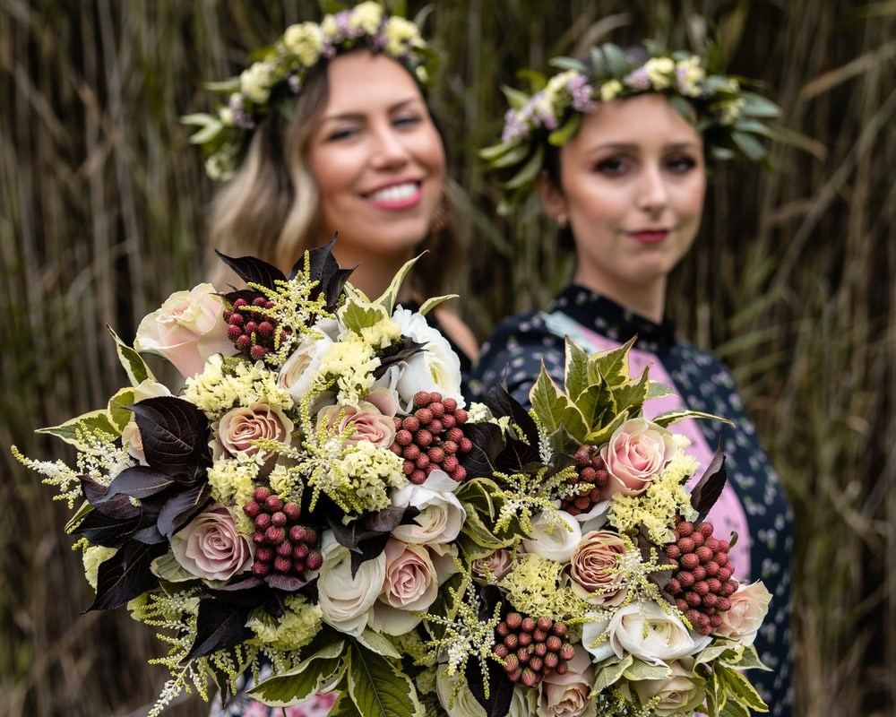 two smiling women holding bouquet of flowers
