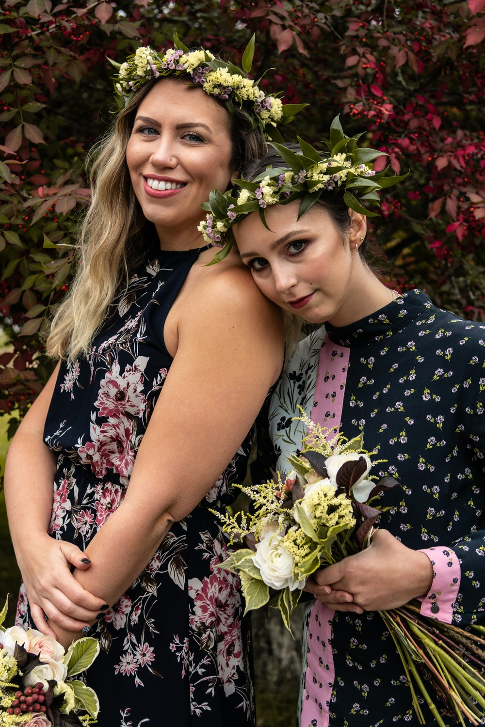 two woman wearing black floral dresses