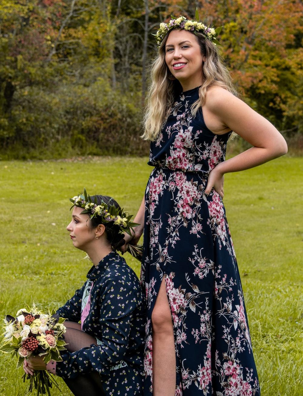 woman wearing floral maxi dress beside woman sitting on green grass field