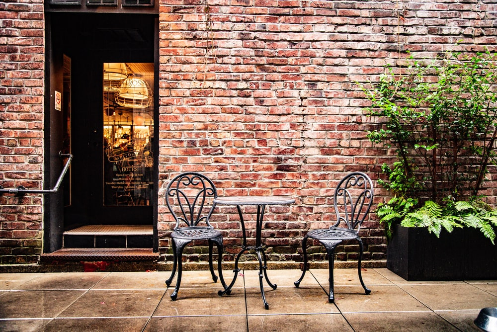 two black empty chairs beside table in front of building