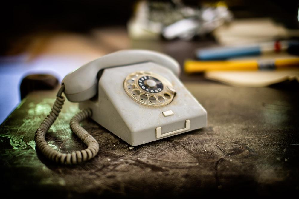 white and brown rotary phone