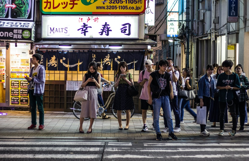 people standing near road beside buildings during night time