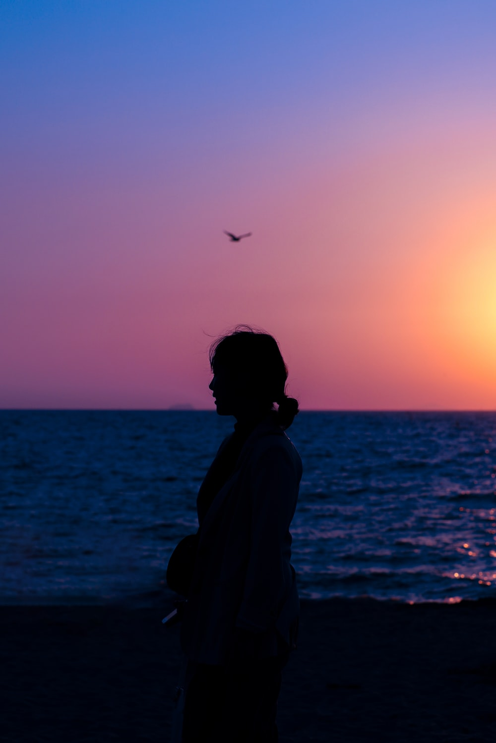 silhouette of woman near ocean