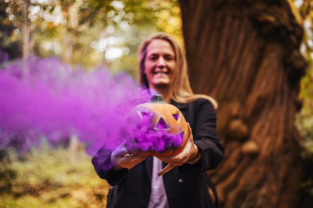 standing person holding Jack-O-Lantern emitting purple smoke