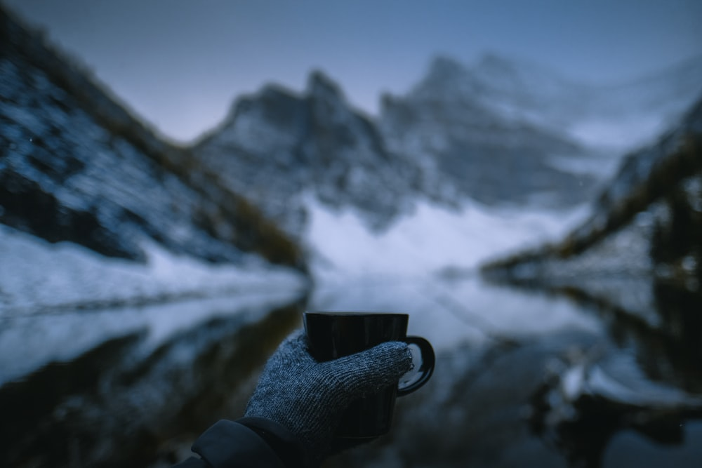 person holding mug near snow capped mountain